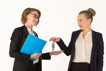realtor gives the keys to a young woman on a white background