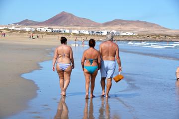 familia caminando por la playa de famara en lanzarote