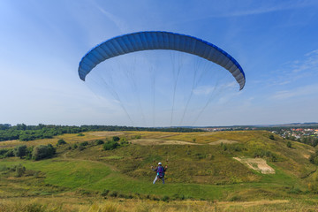 Paraglider flying down the hill