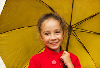 happy girl in a red jacket holding an yellow umbrella