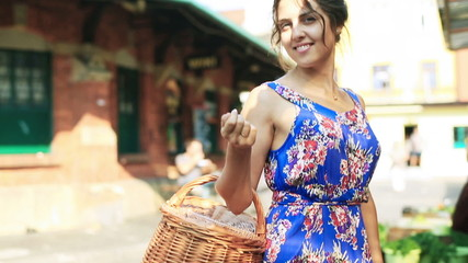 Pretty girl with basket on the fruit market smiling to camera