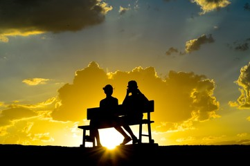 Young people sit on the bench with sunset on the background