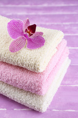 Orchid flower and towels on color wooden background