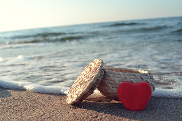 Red heart on white sand beach