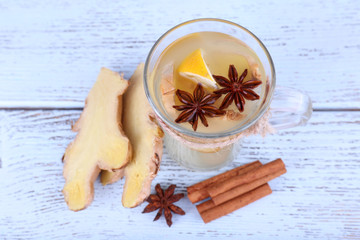 Cup of ginger drink with lemon on wooden background
