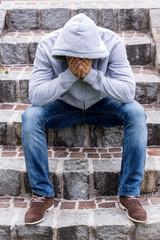 Mann sitzt auf Stufen