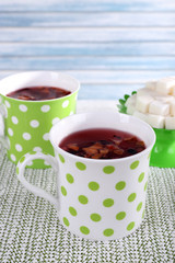 Two cups and sugar on white tablecloth on light background