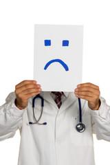 Arzt hält negativen Smiley vor Gesicht