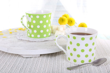 Two polka dot cups of tea on table on curtain background