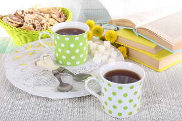 Two cups of tea with biscuits and books