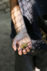 Homeless beggar money on his dirty hands