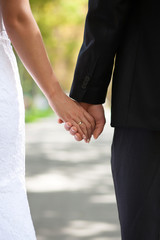 hands of the bride and groom with a wedding ring on the street
