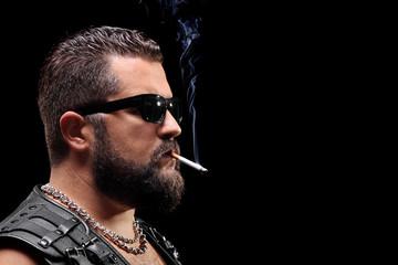 Serious male biker smoking a cigarette