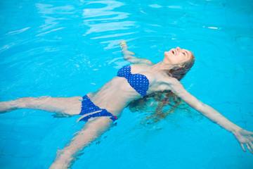 Красивая девушка плавает на спене в бассейне