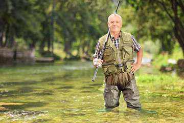 Mature fisherman posing with fishing rod in river