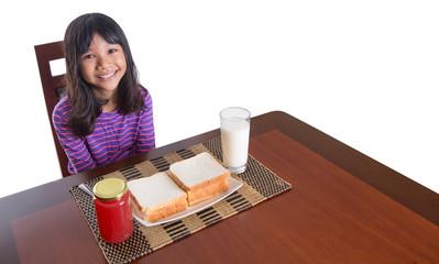 Young Malay Asian preteen girl having breakfast