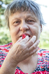 old woman eating berry