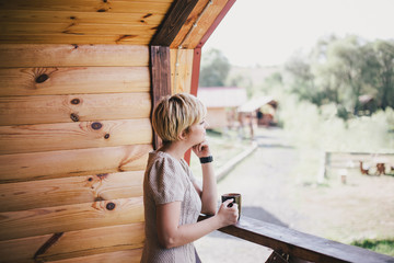 Young woman standing on the cozy balcony with a cup of tea