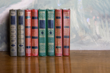 Richly decorated volumes of books with a gold lettering on the b