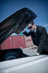 Retro fifties mafia fashion man looking in trunk of vintage car.