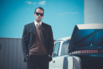 Retro fifties mafia fashion man standing next to open trunk of v
