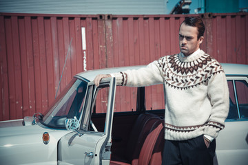Retro fifties fashion man with woolen sweater standing against v