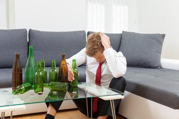 Depressed businessman drunk at home