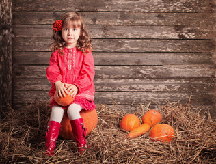 little girl with pumpkin on wooden background
