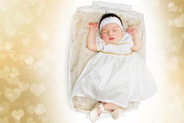 Sleeping newborn baby girl wearing white dress