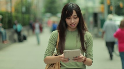 Young Asian Woman in city walking using tablet pc