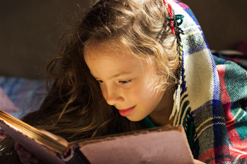portrait of cute  school girl reading an old book at cold day