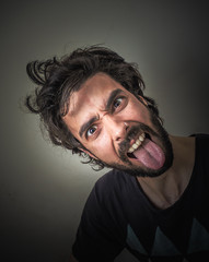 Young bearded and disheveled sticking out her tongue