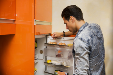 Handsome young man at home looking inside fridge choosing food t