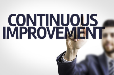 Business man pointing the text: Continuous Improvement