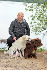 man with 3 dogs near a lake