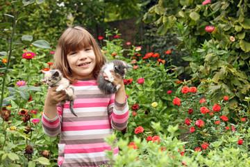 happy little girl holding kittens