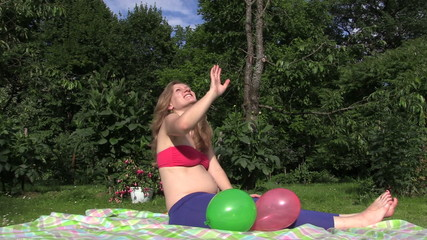 Happy pregnant woman girl play with colorful balloons in garden