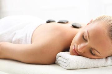 Masaż gorącymi kamieniami, kobieta w salonie spa