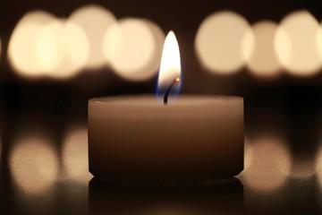 Kerze mit Lichtreflexen im Hintergrund