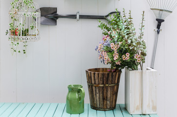 flower on green bench with white wood panel wall in garden