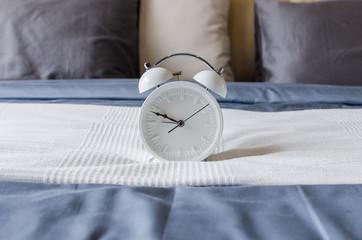 modern white alarm clock on bed