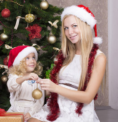 cute little girl with her beautiful mother in Santa's hat
