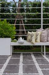 tea set and yellow pillows on white wodden bench