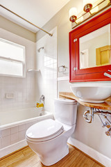 Bathroom interior. Red cabinet with mirror and white vessel sink