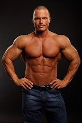 Muscular man poses and shows his muscular body