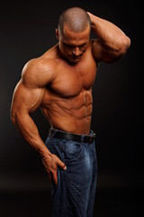 Man poses and shows his muscular body with hands behind head