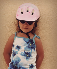Happy small kid girl in pink bike helmet and glasses