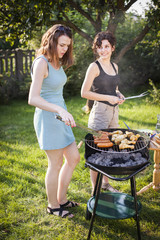 Two pretty girls making food on grill