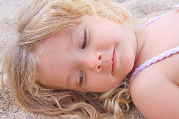 Little girl lying on the sand