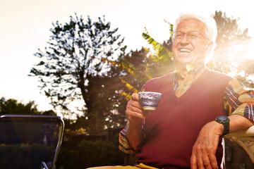 Uomo si rilassa al tramonto in giardino